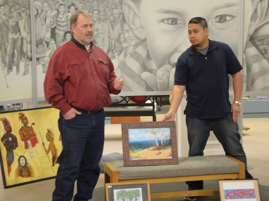 Artist John Chaney, left, talks about his process while Emerald Diamante of the Art Center of Battle Creek listens.