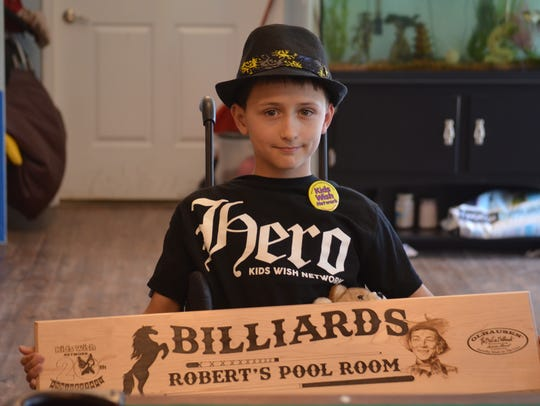9-year old Robert Lilley poses after receiving a pool