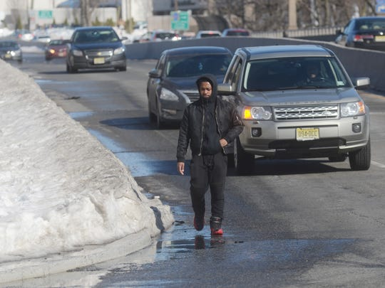 The unplowed sidewalk on the Route 4 overpass above Route 20 in Paterson forced pedestrians to walk in the roadway.