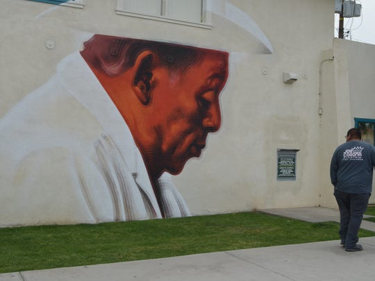 A man stops to look at a mural on the wall of the City