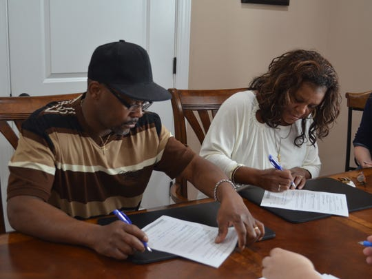 Donelle and Leslie Patterson signing paperwork before