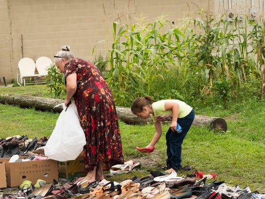 A young girl and a woman look for shoes at Manna From Heaven Outreach.