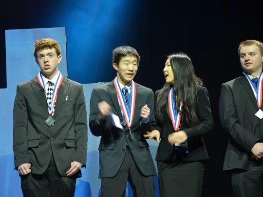 Novi High School students Andrew Lu and Katherine Xie react to winning the award to qualify them for national competition.