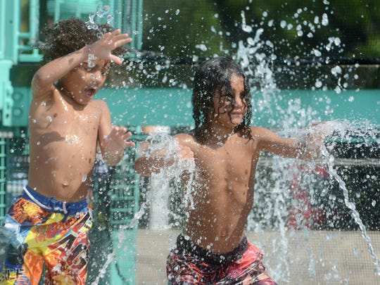 Khalid Williams and his brother, Rasheed, play in a water spout at Pollock Community Water Park in Oshkosh in 2013. The park opens for the season June 10.