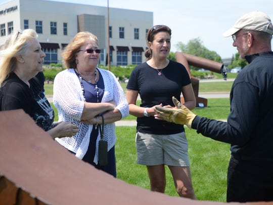 David Korff, right, of the Port Huron Art Initiative, talks about sculptures with Debbie Todd, of Troy; Trish Anderson, of Oxford; and Andrea Rozo, from Colombia, on Saturday in the new sculpture garden along the Thomas Edison Parkway.