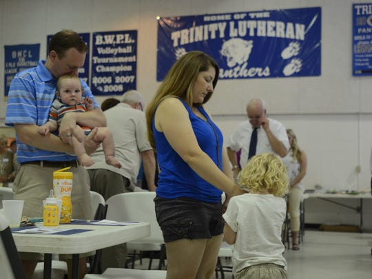 Families and alumni bow their heads in prayer toward the end of Sunday's potluck and farewell ceremony for Trinity Lutheran School in Port Huron.