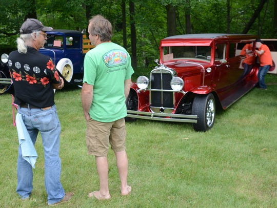 Two men talk while walking around the A&W Classic Car