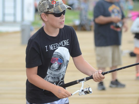 Kolin Korte reels in a large sheepshead during the Algonac Lions Club Pickerel Tournament kids fishing contest.