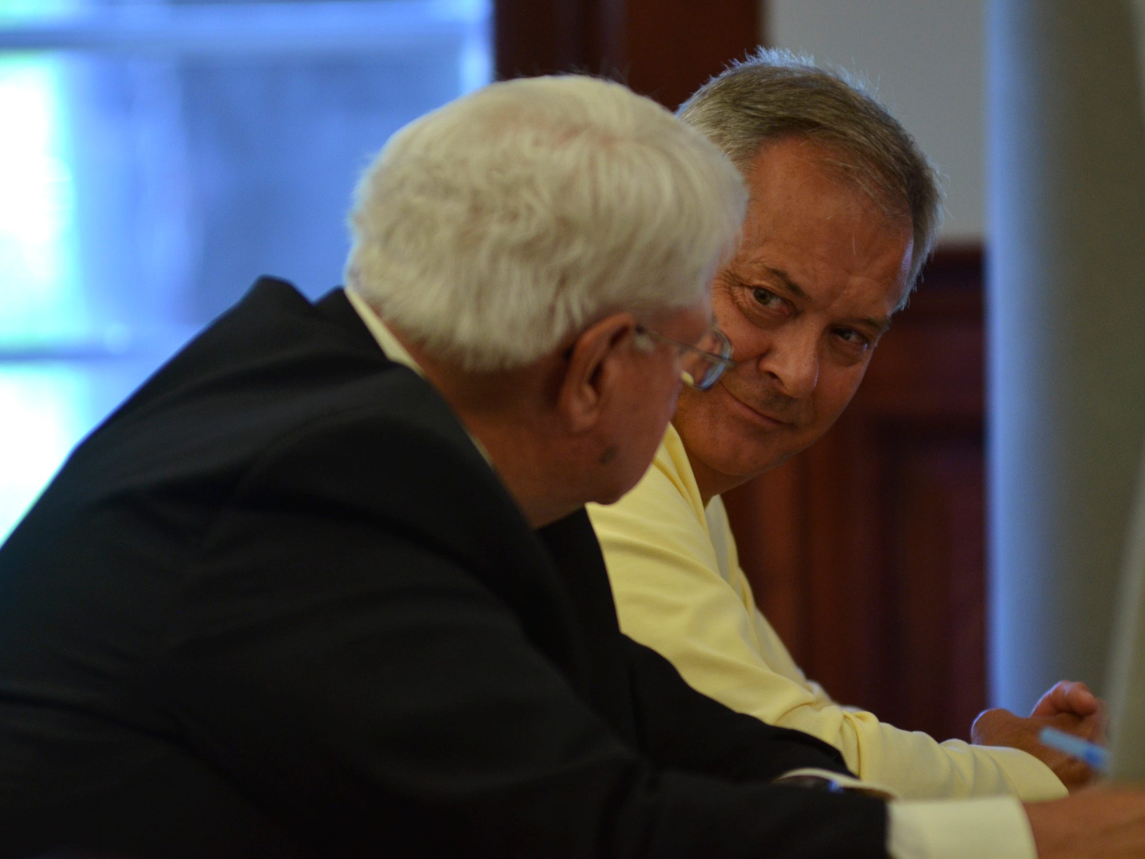 Ken Hatzenbeller looks at his attorney Ken Olson in response to a statement from prosecuting attorney Barbara Harris, of the state auditor's office.