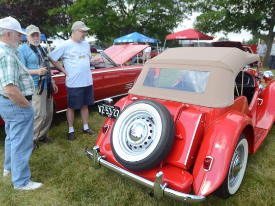 Dave Sickles, left, talks about his 1953 MG TD sports car with Bruno Traks and Charles Johnson.