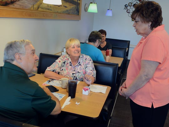 Jeanette Coutelle talks with frequent customers Ken and Deb Semelsberger one last time before she retires from serving.