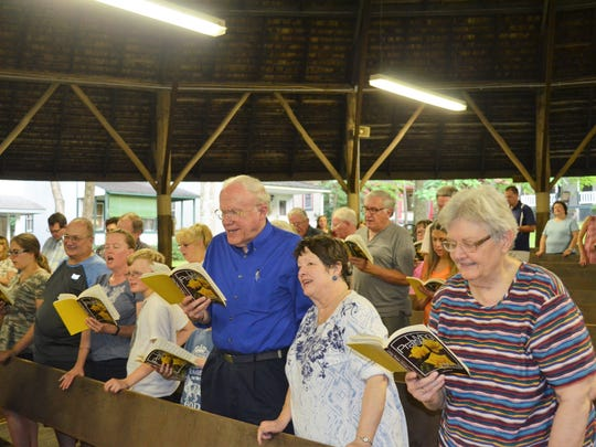 Camp goers raise their voices in song during Wednesday evening's service at the 125th Mt. Lebanon Campmeeting.