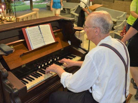 Camp Historian David Shenk plays the pump organ from the 1890s during Wednesday evening's service at the 125th Mt. Lebanon Campmeeting.