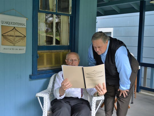 Mt. Lebanon Campmeeting's spiritual director, Rev. Matt Whayland, reviews one of the campmeeting's programs with camp historian David Shenk on the porch of the meeting's museum in 2017.