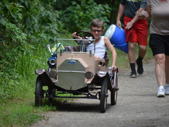 Spencer Anderson, 7, of Elmer drives his Model T go-cart at Parvin State Park during Christmas in July on Saturday. Car enthusiasts were invited to display their cars during the event. Photo/Jodi Streahle