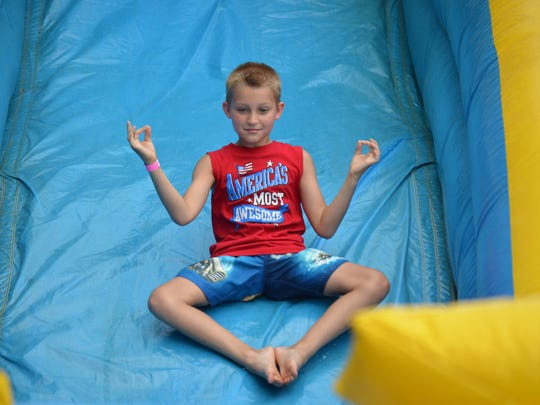 Alex Burgett, 10, of Pennsville maintains a pose as he slides down an inflatable water slide at Parvin State Park during Christmas in July on Saturday, July 22. Photo/Jodi Streahle