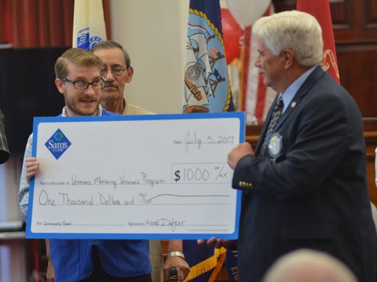 Sam's Club Manager Jordan Smith presents a giant $1,000 check to Joe Parsetich of the Veterans Mentoring Veterans program affiliated with the veterans treatment court in Great Falls.