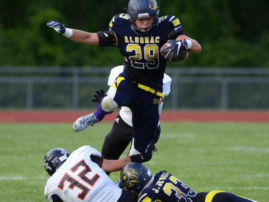 Algonac running back Luke Stephenson jumps over players