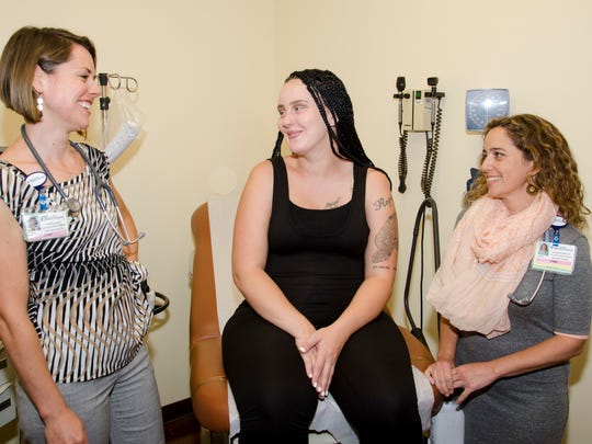 Certified nurse-midwives Joanne Cunha (left) and Jennifer Santos (right) consult with patient Taylor Quabeck.