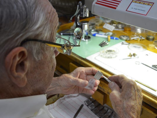 Ralph Hutchinson places the face of a watch he recently repaired in a bag for protection.
