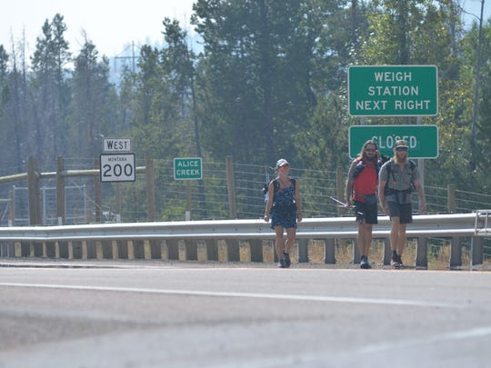Robin Standish, Jeremy Whitehouse and John Weber hike along Highway 200 after being rerouted from the Continental Divide Trail by the Alice Creek Fire.