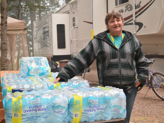 Jo Warneke stands with the water donated by a group