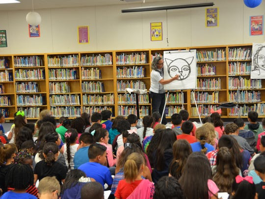 Artist David Diaz draws for students Thursday morning at Ortiz Elementary School. Diaz was the first exhibiting artists at the National Center for Children's Illustrated Literature, in 1997.