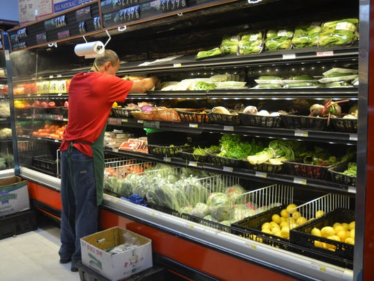 In this file photo, a Happy Mart employee stocks fresh produce. According to the  Bureau of Statistics and Plans, first-quarter consumer data tracked an overall 7.7 percent increase to the cost of food over last year.