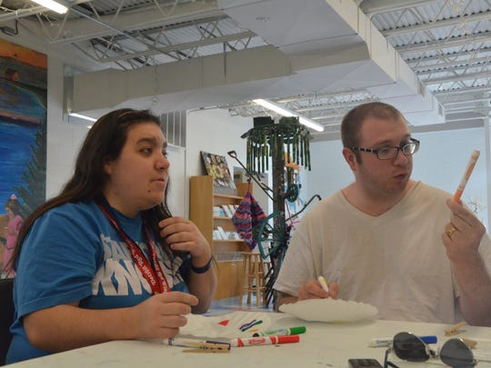 Haley Frederick, left, and Wesley Powers work on creating butterflies during the Community Inclusive Recreation's Saturday art class.