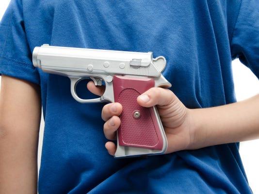 Little boy taking gun behind his back dangerous