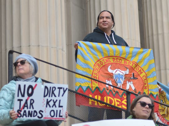 Lance Four Star holds a flag representing the Hudesana, or Red Bottom Clan of the Assiniboine Tribe. From Wolf Point, Four Star is concerned the Keystone XL pipeline spur planned to run through the Fort Peck Indian Reservation would pose a threat to communinty drinking and irrigation water.