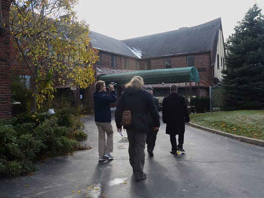 Members of the media walk through the St. Clair Inn