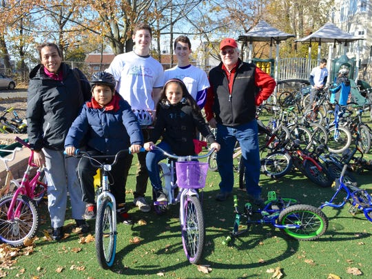Jason and Adriana Reyes ride away on new bicycles with help from Matt Shapiro, Brian Johnson and Kas Kasprowicz.
