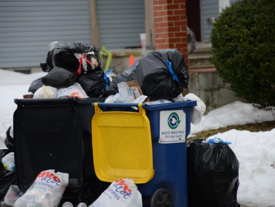 Trash overflowing a recycling bin at a Georgetown home.