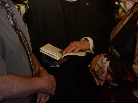 The Rev. Pat Thompson blessing wedding rings for Rose