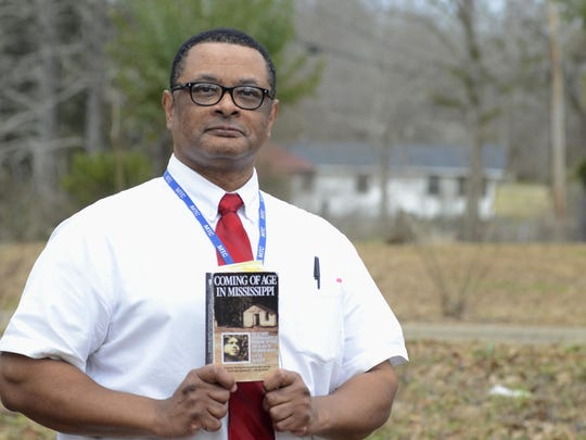 """Roscoe Barnes holds a copy of Anne Moody's book, """"Coming of Age in Mississippi,"""" near the author's childhood home, seen in background, in Centreville. Moody's involvement in the civil rights movement put her at the epicenter of key historical events, Barnes said. (Matt Williamson/The Enterprise-Journal via AP)"""