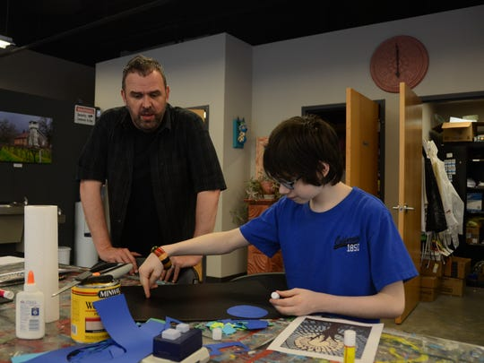 """Art Inspired Academy teacher Richard White works with Keegan Nace on a mosaic project with the addition of a Tardis from """"Doctor Who."""""""
