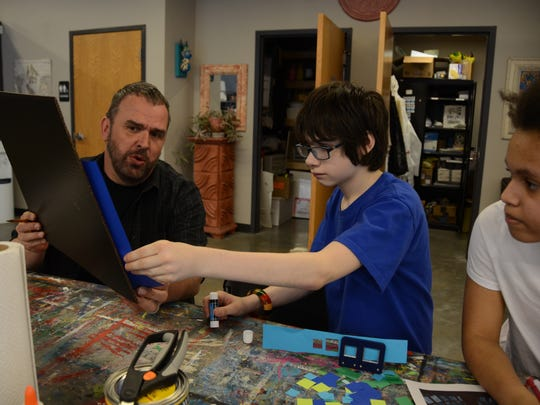 Teacher Richard White shows student Keegan Nace how he could arrange his mosaic during a recent art class.