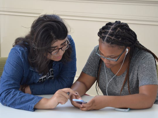 Vassar College student Laura Zapien, a counselor at Vassar's Digital Literacy smartphone camp, works with Sirena Fitzgerald, a Poughkeepsie Middle School student enrolled in the camp.