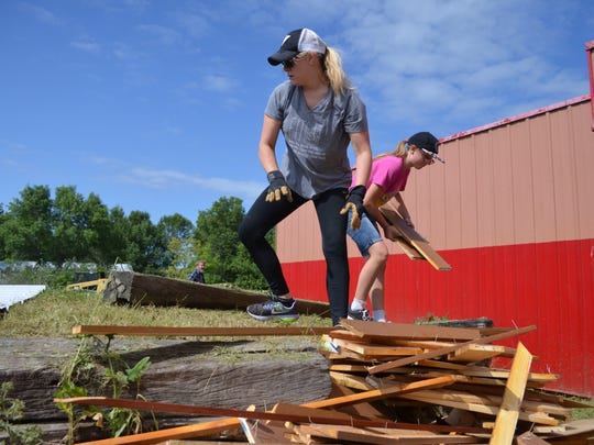 North Ridge Church congregation members help clear out and organize debris from Saturday's partial demolition of the former Rear End bar and strip club.