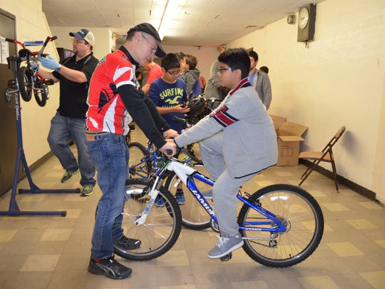 Westchester Cycle Club member Bob Herman fits a youngster for a bicycle,