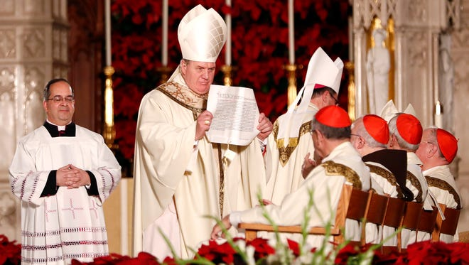 Joseph Tobin, center, shows a declaration read by Christopher Pierre, apostolic nuncio of the United States, which installed Tobin as the new archbishop of Newark during a Mass ceremony Friday in Newark.