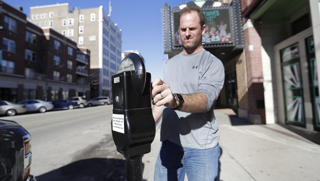 Troy Lasecki feeds a parking meter on the east side of the 100 block of Washington Street in Green Bay.