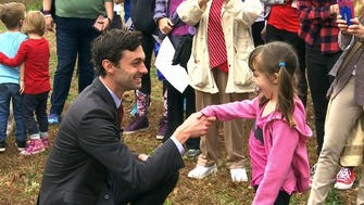 In a March file photo, Democratic congressional candidate Jon Ossoff is seen with supporters outside of the East Roswell Branch Library in Roswell, Ga.