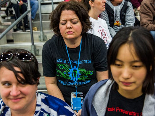 Christy Kobes, center, prays before her son competes