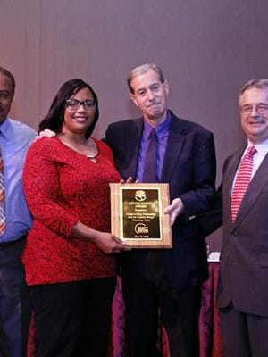 From left to right, Det. Keith James (Camden County Police Department), Meishka Mitchell (Cooper's Ferry Partnership), and Chuck Giacobbe (Camden County Office of Environmental Affairs) accept the Open Space Award from NJCCC President Patrick Ryan.