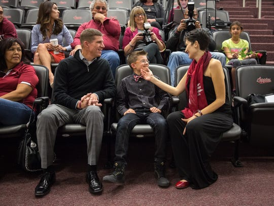 Lori Paulson talks to her son, 9-year-old Jeremiah Young, at New Mexico State University's Hall of Legends while her husband Brandon Young looks on. NMSU held a reception in January to name the football team meeting room after Paulson, who is battling pancreatic cancer, recognizing her efforts as honorary captain and her family's donation of $100,000 to the football program.