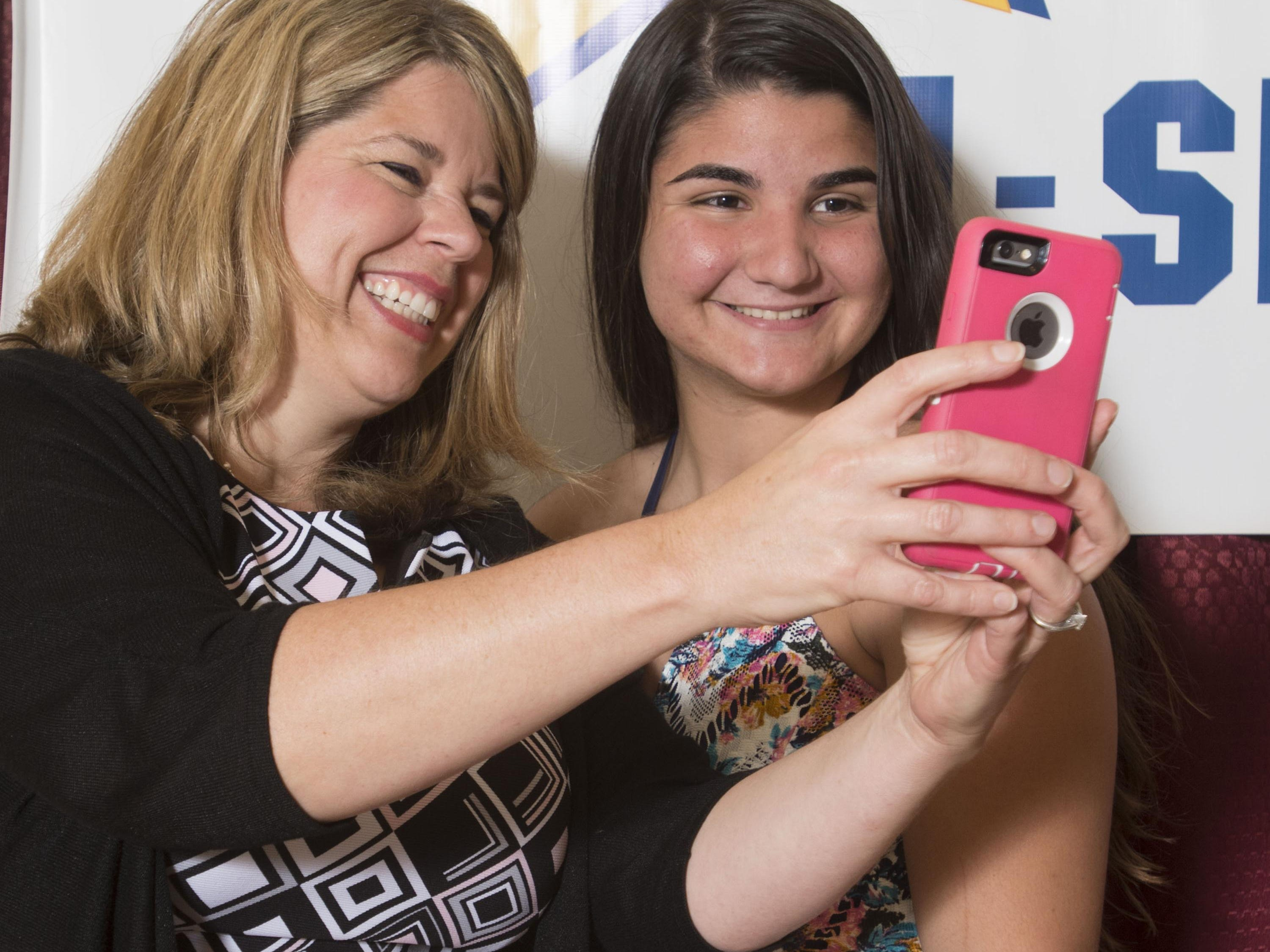 Attorney Kim Adams, left, takes a selfie with Olivia Brahms, right, the female Troy Rafferty Scholarship winner, during the Pensacola News Journal All-Sport Awards Banquet Wednesday night.