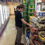 Matthew Lawhead, a student at Bridge Alternative High School, places stickers that discourage underage drinking on packs of alcoholic beverages at a Brighton-area party store. The effort was part of a campaign known as Project Sticker Shock.