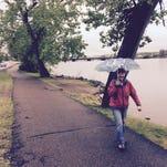 Joanne Bernard goes for a walk in the rain Saturday along the River's Edge Trail.